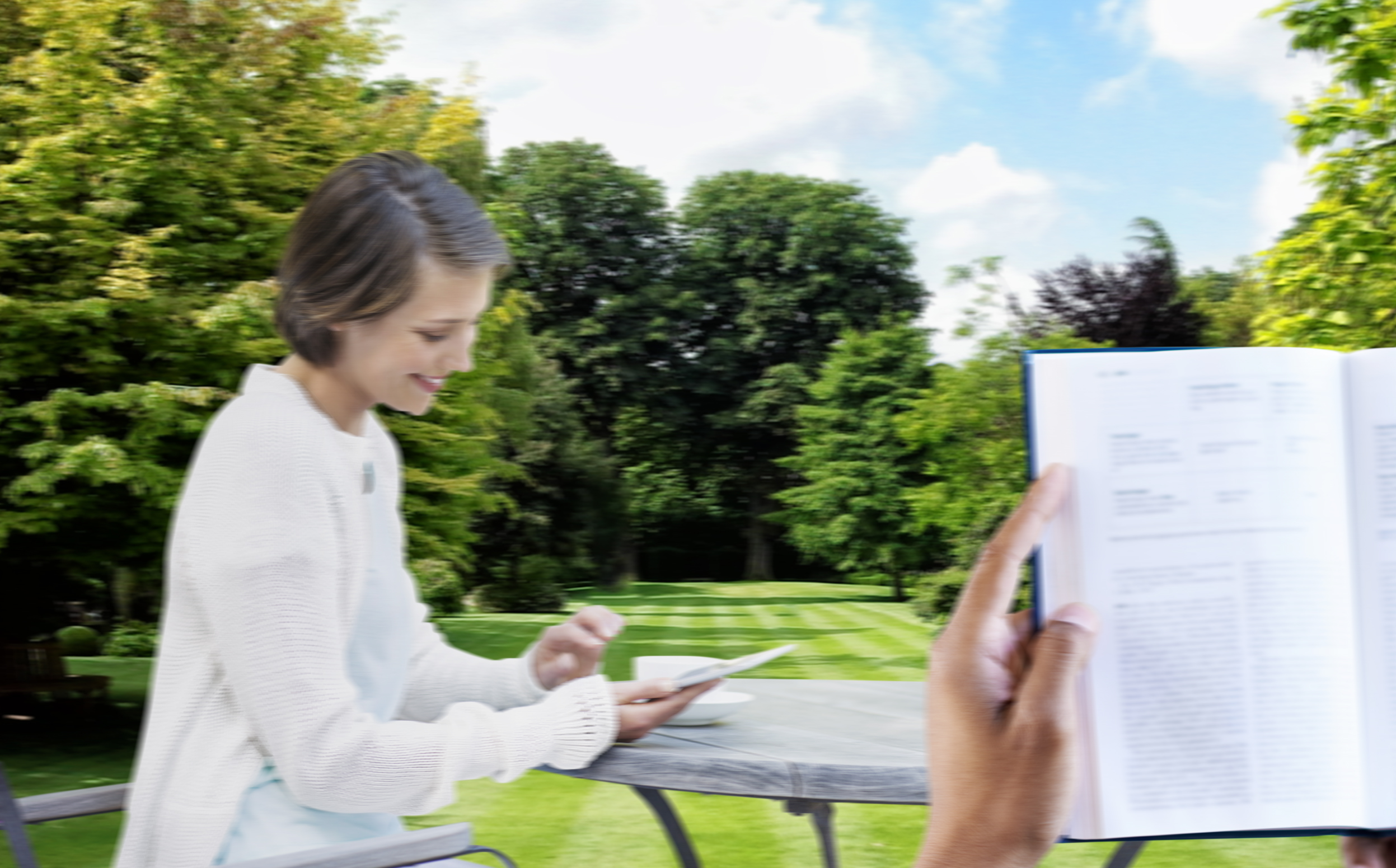 Woman using digital tablet at table outdoors